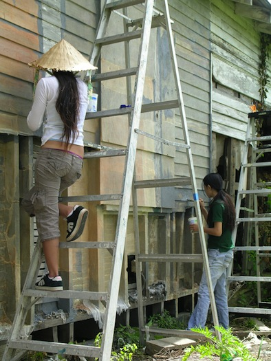 Volunteers Tuyen Nguyen and Tuyet Nguyen applying latex to the shotgun house exterior. Photo by Takashi Horisaki.