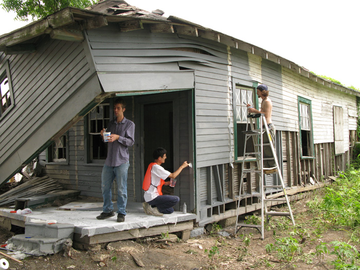 Horisaki and volunteers James Goedert and Kyle Throssell applying latex to the shotgun house exterior.