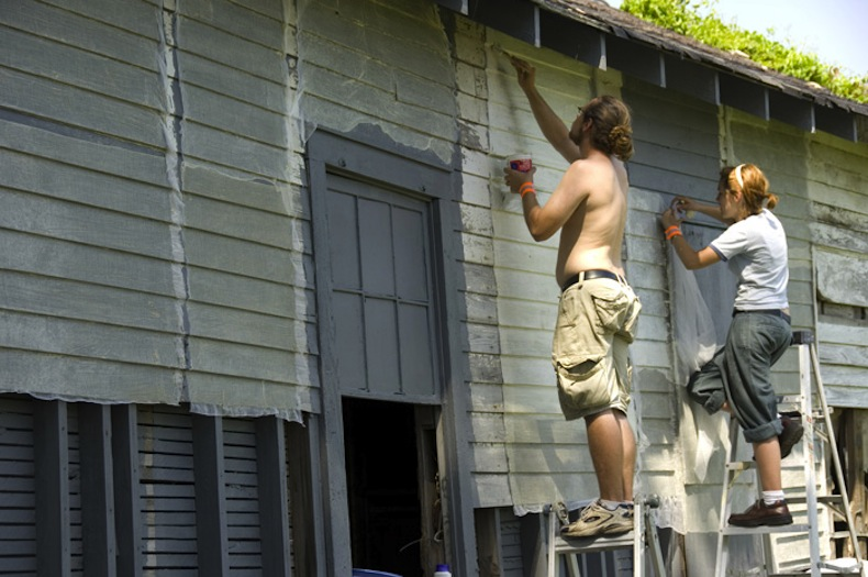 Volunteers Stu Hollins and Rebecca Parker applying latex and cheesecloth to the shotgun house exterior. Photo by Jurgen Vogt.