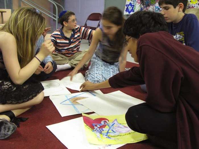 Queens teens discussing interpretation of kids' drawings with youth group at local Jewish temple.